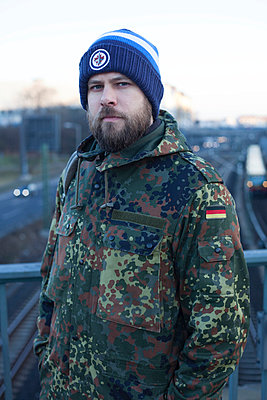 Man in camouflage coat - p906m946045 by Wassily Zittel