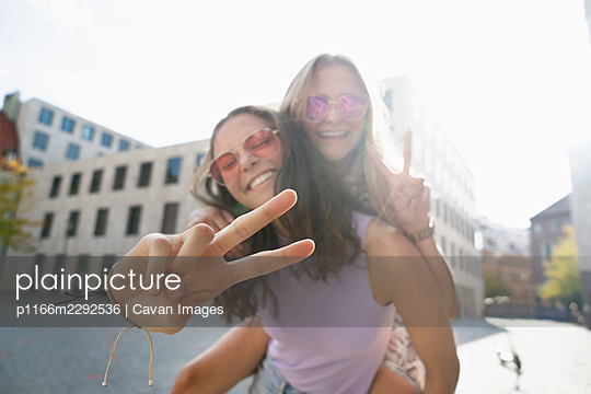 Two young women giving eachother piggybackride And Laughing At Camera - p1166m2292536 by Cavan Images