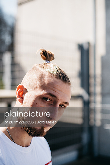 Young man with pigtail and tattoo - p1267m2263396 by Jörg Meier