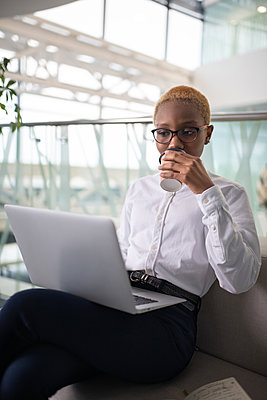 African American businesswoman drinking coffee and using laptop - p1166m2280901 by Cavan Images