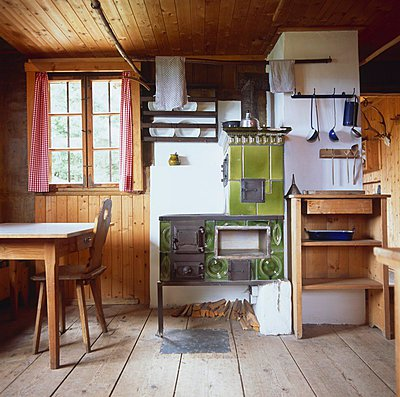 Rustic kitchen-utility room with tiled stove and broad, rough floorboards - p1183m997749 by Schaun, Jeanette