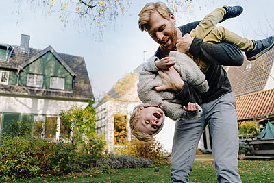 Happy father playing with son in garden - p300m2167245 by Kniel Synnatzschke
