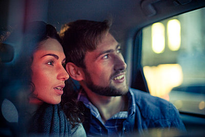 Couple looking out car window at night - p623m1221426 by Gabriel Sanchez