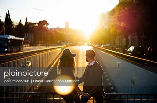 Couple looking away while sitting on bridge railing together at city during sunset - p300m2227031 by Oscar Carrascosa Martinez