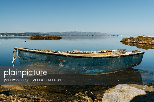 Abandoned rowboat moored in lake against clear sky on sunny day at natural park, Ebro Delta, Spain - p300m2250098 by VITTA GALLERY