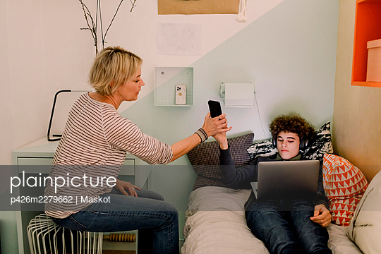 Boy giving smart phone to mother while lying with laptop on bed t home - p426m2279662 by Maskot