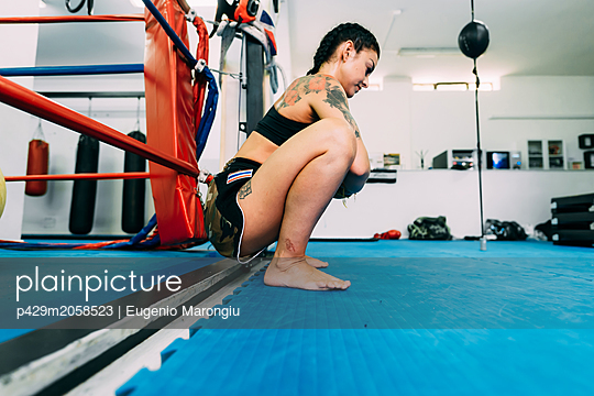 Female boxer squatting by boxing ring ropes - p429m2058523 by Eugenio Marongiu