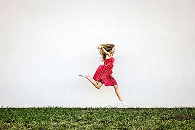 Weiblicher Teenager läuft über eine Wiese - p1019m1496306 von Stephen Carroll