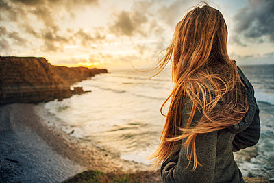 Side view of woman looking at view while standing at beach - p1166m1186557 by Cavan Images