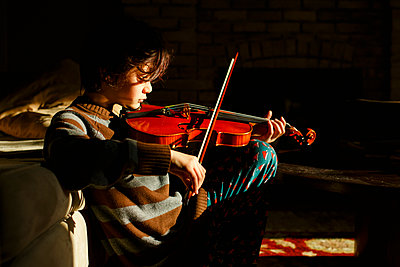 A beautiful boy sits in a patch of sunlight playing a red violin - p1166m2190543 by Cavan Images