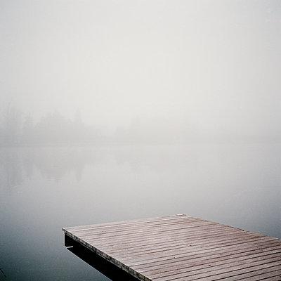 Deserted boardwalk by thelake in the fog - p1287m2288683 by Christophe Darbelet