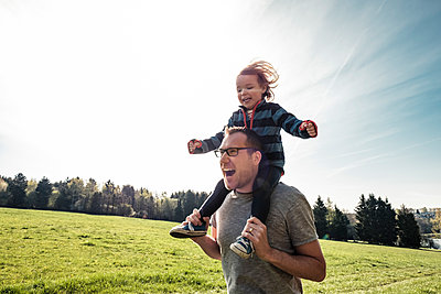 Portrait of father carrying little daughter on his shoulders - p300m2166944 by Wilfried Feder