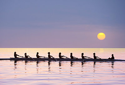 Silhouette of rowing team practicing on still lake - p555m1410891 by Pete Saloutos