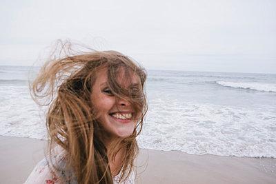 Junge Frau mit wehenden Haaren am Strand - p586m962883 von Kniel Synnatzschke