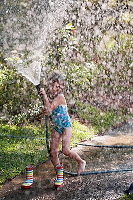 Girl playing with water hose on sidewalk - p924m1125691f by Kinzie Riehm