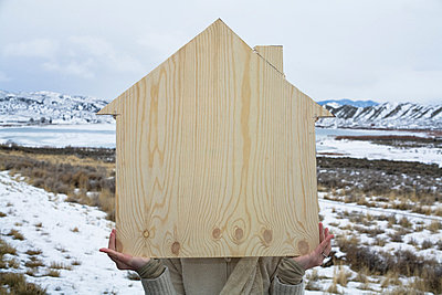 Person outdoors holding a wooden shape of a house - p924m665103 by Mallon Industries