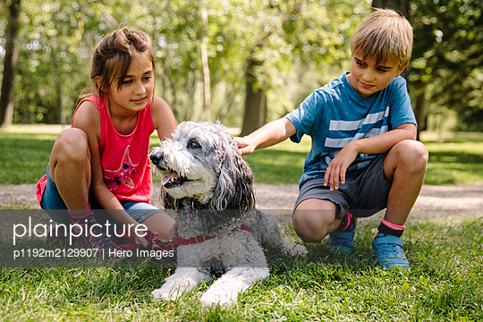 Two children with pet dog on the grass - p1192m2129907 by Hero Images