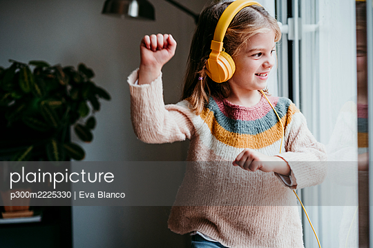 Girl wearing headphones dancing while standing by window at home - p300m2225330 by Eva Blanco