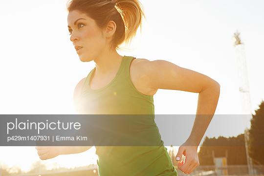 Female runner running in sunlit park - p429m1407931 by Emma Kim