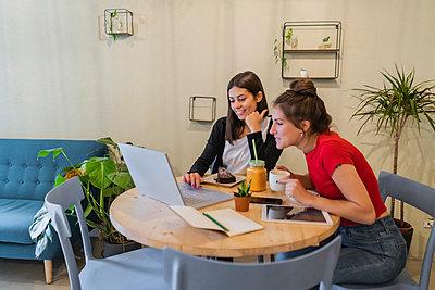 Two young women using laptop in a cafe - p300m2140381 von Giorgio Fochesato