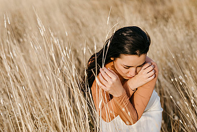 Thoughtful young woman sitting amidst grass in field at sunset - p300m2256640 by Tania Cervián