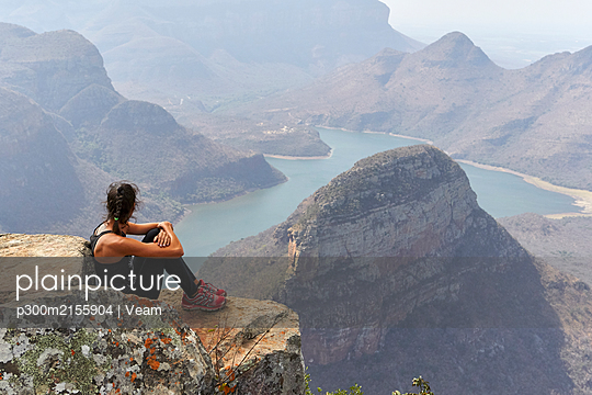 Woman sitting on a rock with beautiful landscape as background, Blyde River Canyon, South Africa - p300m2155904 by Veam