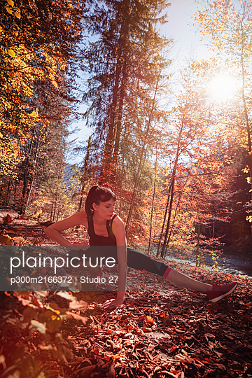 Woman jogging in autumn forest, stretching for warm up - p300m2166372 von Studio 27