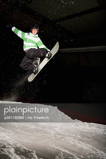 Snowboarder mid-air on a ski slope
