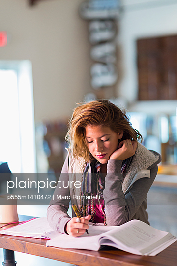 Mixed race student studying at table - p555m1410472 by Marc Romanelli