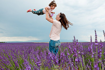 Woman throwing little girl in the air among lavender fields in summer - p1166m2136639 by Cavan Images
