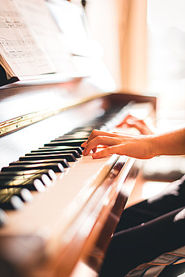 Cropped image of child's hands playing piano in a sunny room. - p1166m2153757 by Cavan Images