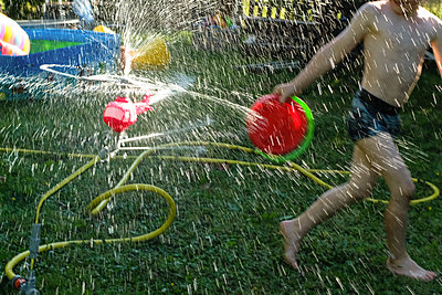 Summer fun with lawn sprinkler - p236m1585874 by tranquillium