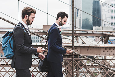USA, New York City, two businessmen with cell phones and earbuds on Brooklyn Bridge - p300m1204722 by Uwe Umstätter