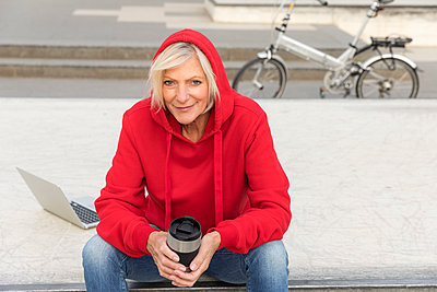 Senior woman wearing red hoodie sitting outdoors with laptop and takeaway coffee - p300m2004728 by Jo Kirchherr