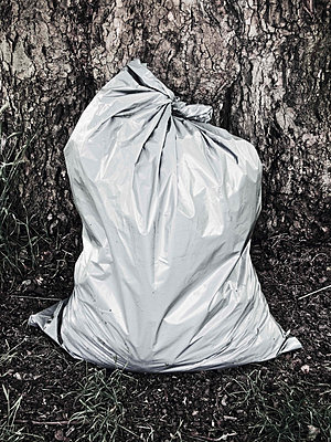 One Full Grey Plastic Bag Standing In Front Of Tree - p3200458 by Jens Haas