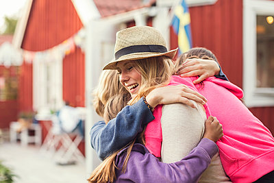 Happy friends embracing in back yard - p426m1226249 by Maskot