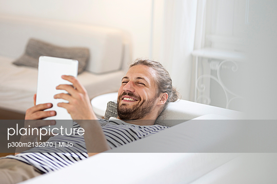 Smiling young man lying on couch at home using tablet - p300m2132370 von MiJo