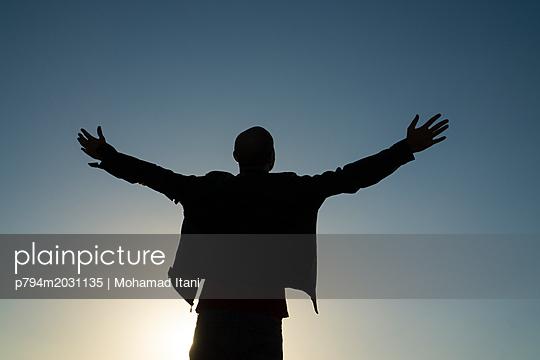 Silhouette eines Mannes mit ausgestreckten Armen - p794m2031135 von Mohamad Itani