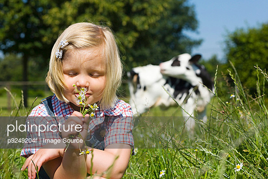 A girl smelling wildflowers - p9249204f by Image Source