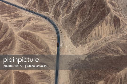 Aerial view of rural road through desert landscape, Nazca, southern Peru. - p924m2196772 by Guido Cavallini