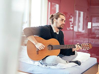 Alternativer, junger Mann beim Gitarre spielen auf Bett - p1358m1215566 von Nolting