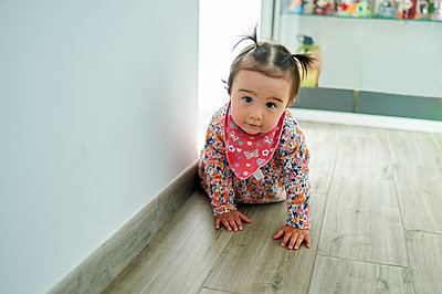 Cute toddler crawling on floor by wall at home - p300m2275682 by Kiko Jimenez