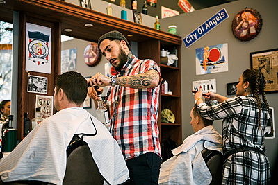 Barbers cutting customer´s hair - p352m2121613 by Folio Images