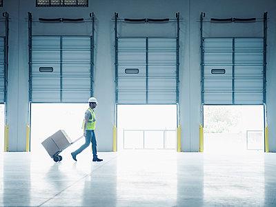 Indian worker pulling hand truck near open loading dock doors - p555m1305138 by Erik Isakson