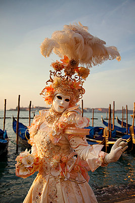 Venice, Veneto, Italy, A mask posing in front of gondolas at the bacino di San Marco during carnival. - p652m716791 by Ken Scicluna