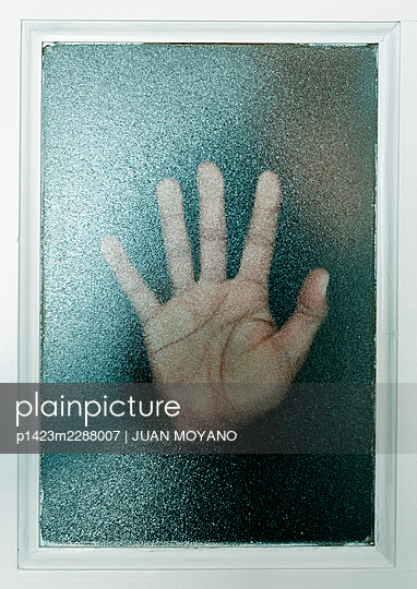 Man hand against a translucent glass door or window - p1423m2288007 by JUAN MOYANO