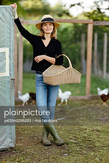 Junge Frau holt Eier vom Hühnerhof - p432m2295253 von mia takahara