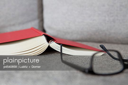 Book and glasses on a sofa - p4540858 by Lubitz + Dorner