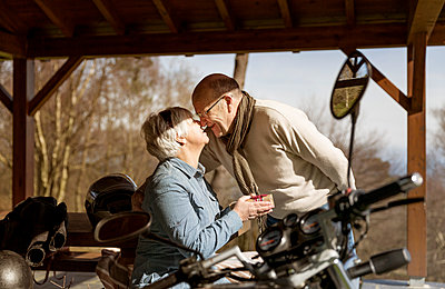 Happy senior couple rubbing noses in gazebo by motorcycle - p1166m1144767 by Cavan Images