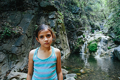 Portrait of confident girl standing against waterfall in forest - p1166m1489684 by Cavan Images